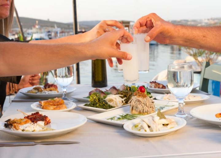 Friends enjoying ouzo alongside their meal - Nadir-Keklik/Shutterstock.com